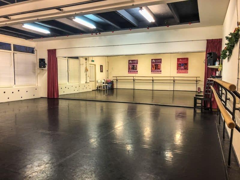 Danszaal met grote spiegel en dansbar